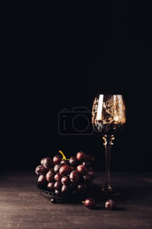 Photo for Delicious ripe grapes and glass of red wine on wooden table on black - Royalty Free Image