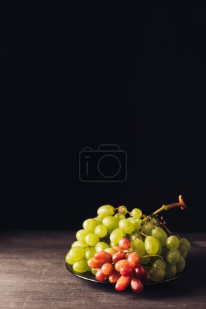 close-up view of fresh ripe juicy grapes on wooden table on black