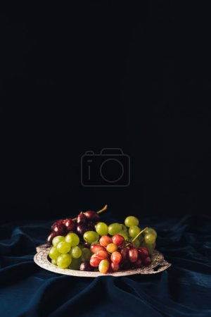close-up view of various types of grapes on vintage plate on dark fabric on black background