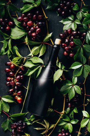 top view of fresh ripe grapes, green leaves and bottle of wine on black wooden surface