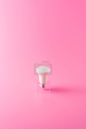 close-up view of single light bulb on pink background