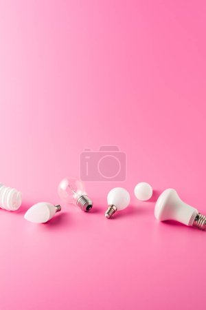 various types of light bulbs on pink background
