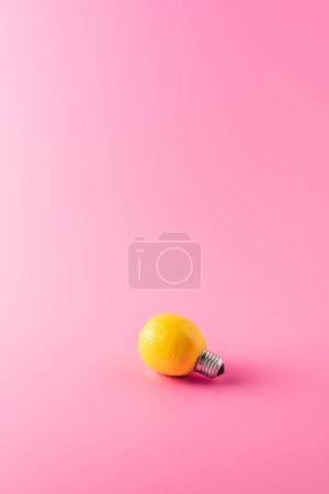 close-up view of light bulb made of lemon on pink