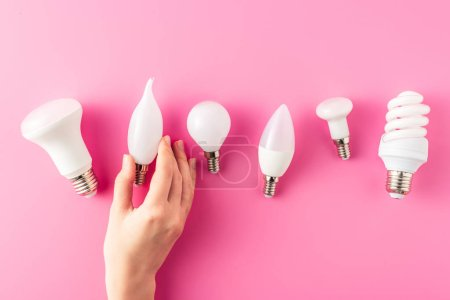 partial top view of human hand and various types of light bulbs on pink