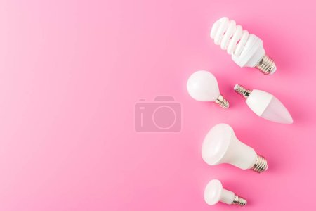 top view of various types of lamps on pink background