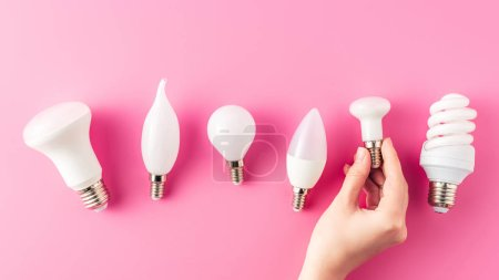 cropped shot of human hand and various types of light bulbs on pink