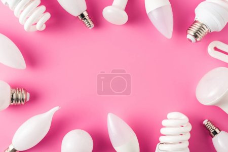 top view of various light bulbs on pink background, energy concept