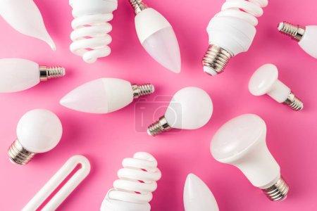 Photo pour Vue de dessus de diverses ampoules sur fond rose - image libre de droit