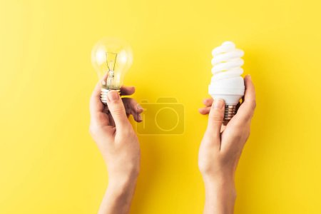cropped shot of person holding different types of light bulbs on yellow