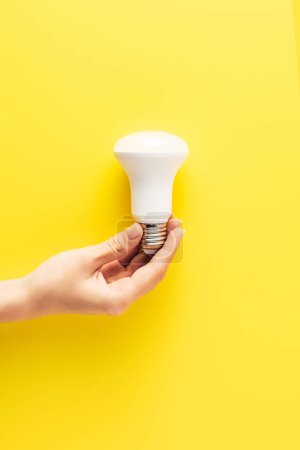 Photo for Close-up partial view of person holding light bulb on yellow - Royalty Free Image