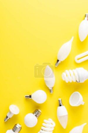 Photo pour Vue de dessus de différents types d'ampoules sur fond jaune - image libre de droit