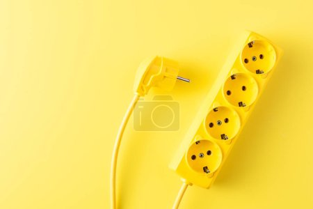 Photo for Top view of yellow socket outlet and plug on yellow background - Royalty Free Image