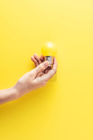 cropped shot of person holding yellow light bulb on yellow background
