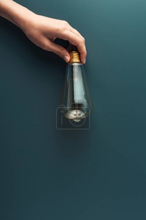 cropped shot of human hand holding light bulb on grey background