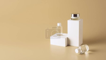 close up view of micellar water in bottles and face cream in glass jar on white cubes on beige backdrop