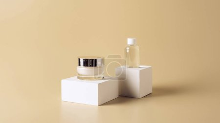 close up view of micellar water and body cream on white cubes on beige background
