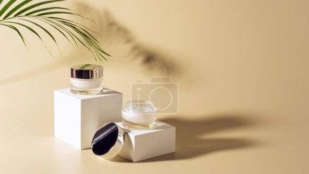 Photo pour Bouchent la vue de palm leaf, du visage et du corps crèmes en bocaux de verre sur des cubes blancs sur fond beige - image libre de droit