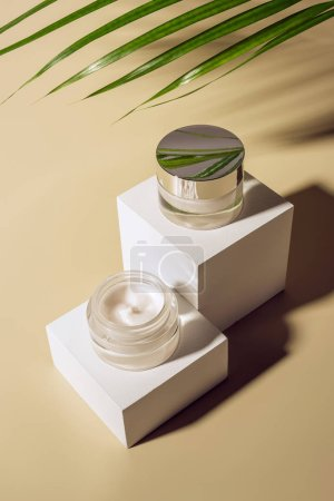 close up view of palm leaf, body creams in glass jars on white cubes on beige background