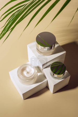 close up view of green palm leaf and body creams in glass jars on white cubes on beige background