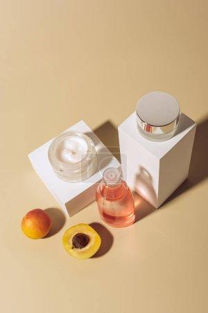 Photo pour Gros plan sur abricots, crèmes pour le visage et lotion hydratante sur fond beige - image libre de droit