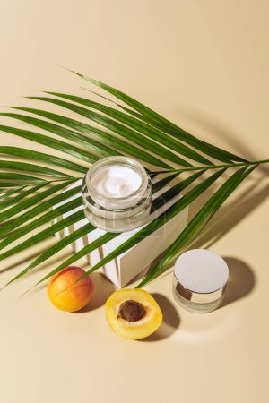 close up view of skin care products, apricots and green palm leaf on beige backdrop