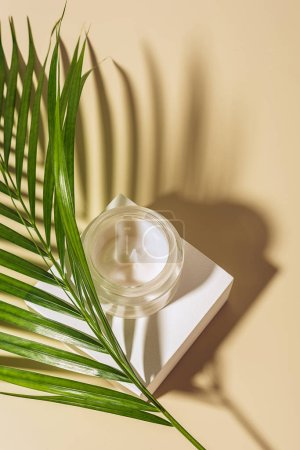 close up view of moisturizing cream in glass jar with palm leaf on beige background