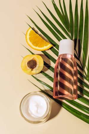top view of body cream and lotion, fruits and green palm leaf on beige background