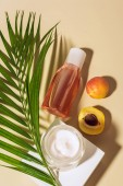flat lay with body cream and lotion, apricots and green palm leaf on beige background