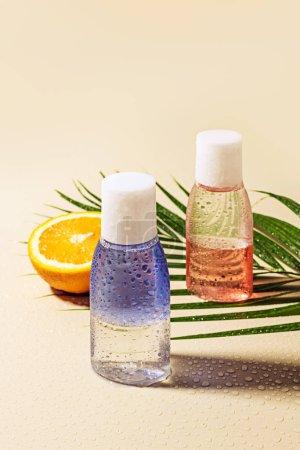 Photo pour Bouchent la vue sur l'eau micellaire en bouteilles, feuille de palmier vert et orange la moitié avec de l'eau tombe sur fond beige - image libre de droit