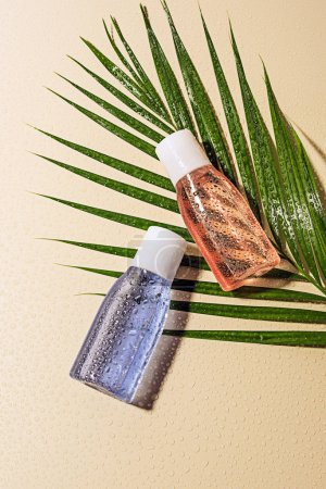 flat lay with lotions in bottle on green palm leaf with water drops on beige background