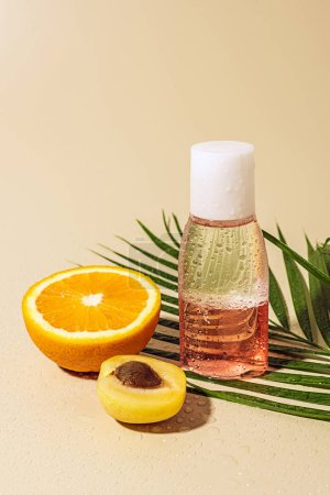 Photo for Close up view of micellar water for skin care in bottle and orange half on beige background - Royalty Free Image