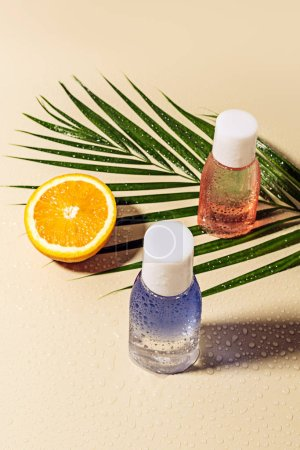 close up view of micellar water in bottles, green palm leaf and orange half with water drops on beige backdrop
