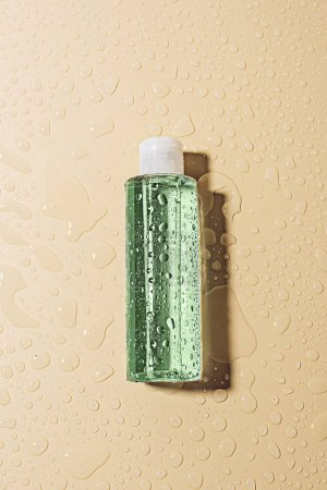 top view of micellar water with water drops on beige background