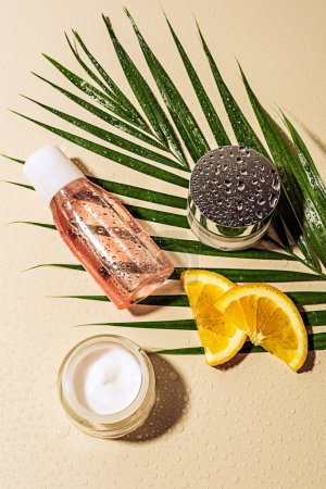 flat lay with skin care products, green palm leaf and orange slices with water drops on beige backdrop