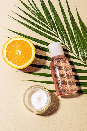 top view of facial cream and lotion, palm leaf and orange half with water drops on beige background