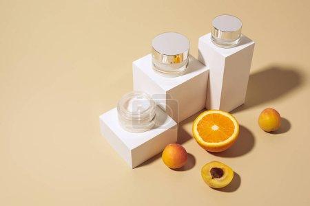 Photo pour Bouchent la vue de fruits et crèmes de soins disposées sur la toile de fond beige - image libre de droit