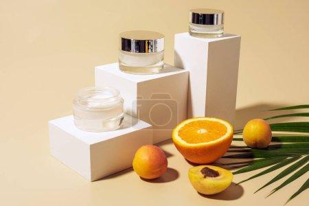 Nahaufnahme arrangierter Hautpflegecremes, Früchte und Palmblätter auf beigem Hintergrund