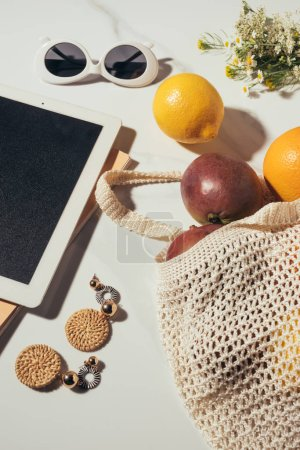 close-up view of digital tablet, sunglasses, earrings, flowers and string bag with fresh tropical fruits