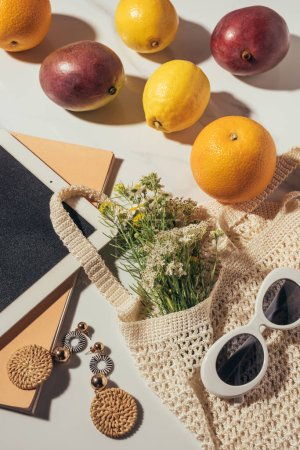 top view of digital tablet, earrings, sunglasses, flowers and string bag with fresh ripe fruits