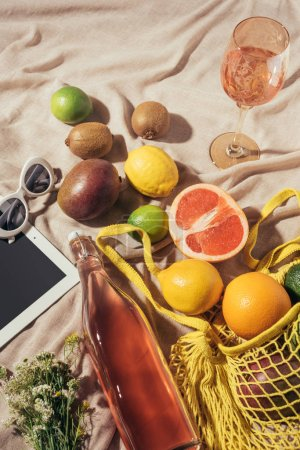 top view of glass and bottle with summer drink, digital tablet, sunglasses and string bag with fresh fruits