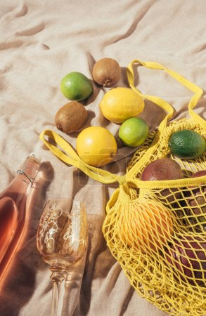 top view of glass, bottle with summer drink and yellow string bag with fresh ripe tropical fruits
