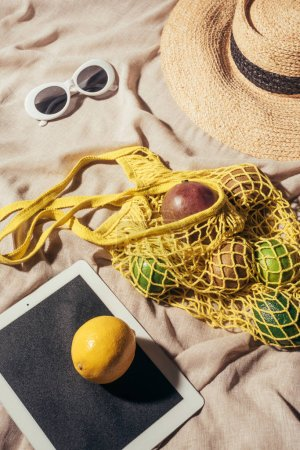 high angle view of digital tablet, sunglasses, straw hat and string bag with ripe fruits