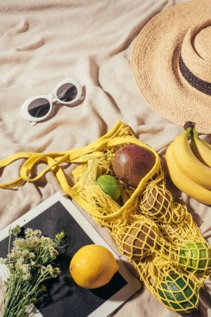 top view of straw hat, sunglasses, flowers, digital tablet and string bag with ripe fruits