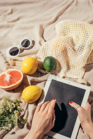cropped shot of person using digital tablet and string bag with fresh fruits and sunglasses