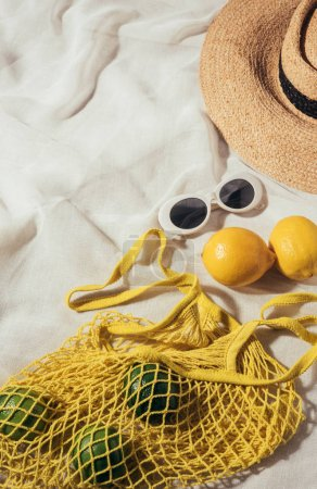 high angle view of sunglasses, wicker hat and string bag with fresh ripe tropical fruits