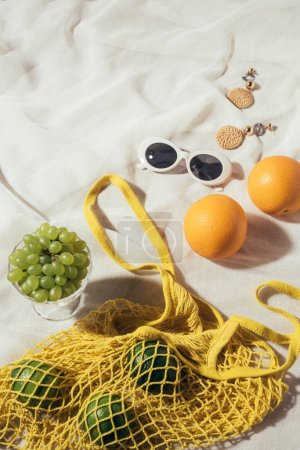 high angle view of sunglasses, earrings and yellow string bag with fresh fruits