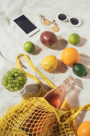 high angle view of smartphone, sunglasses, earrings and string bag with fresh fruits