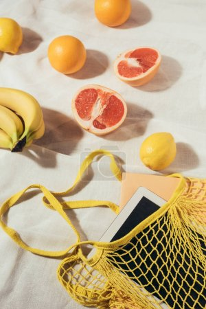 digital tablet in yellow string bag and fresh ripe tropical fruits