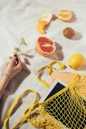 cropped shot of human hand and string bag with digital tablet and fresh ripe fruits