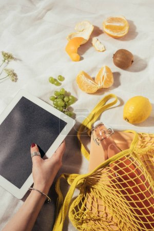 cropped shot of person using digital tablet and string bag with glass bottle and fresh fruits